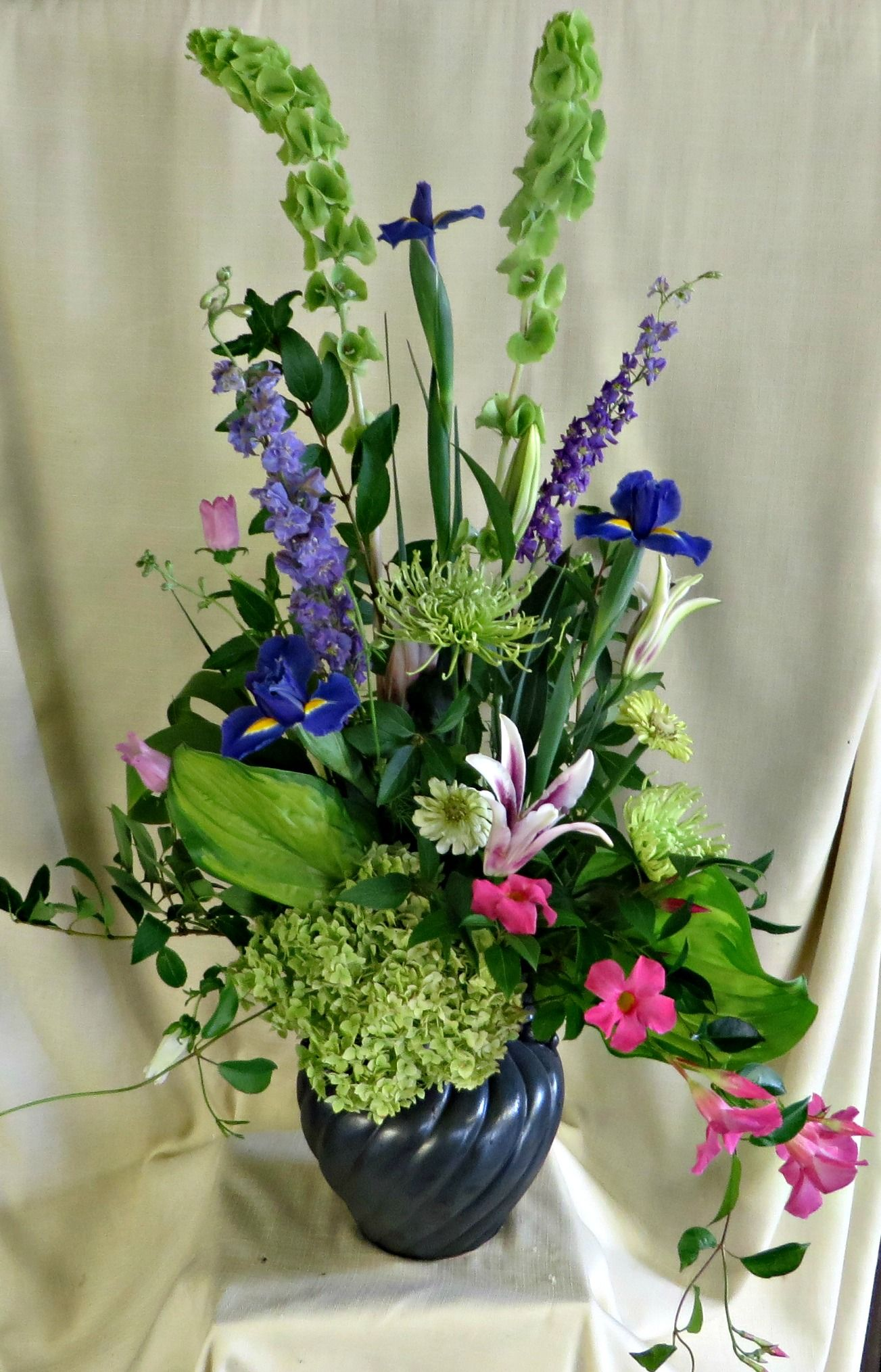 Funeral flowers urn with lilies bells of ireland larkspur iris funeral flowers urn with lilies bells of ireland larkspur iris and hydrangea izmirmasajfo