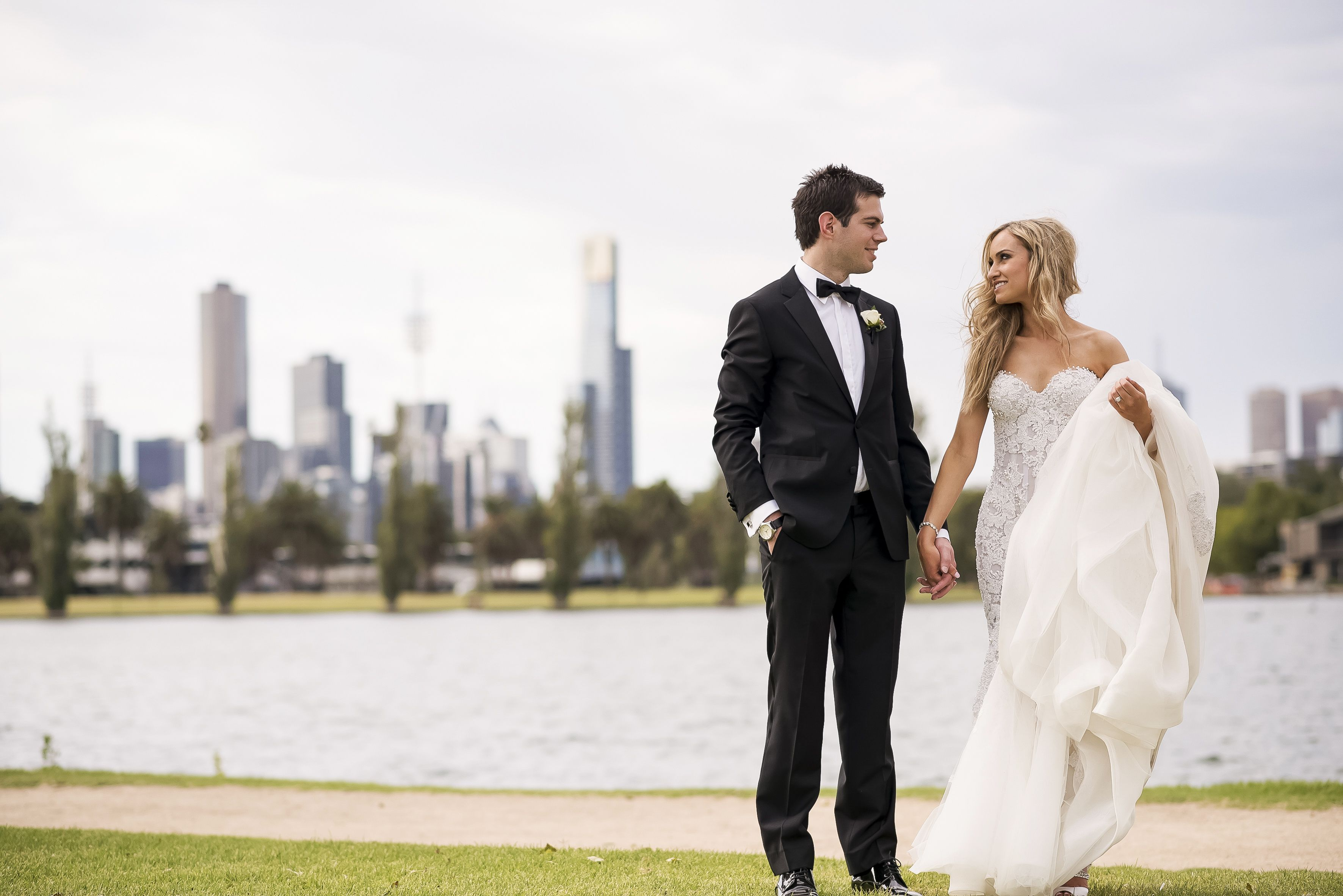 Bride in Steven Khalil wedding dress and groom in tuxedo and Melbourne backdrop | itakeyou.co.uk
