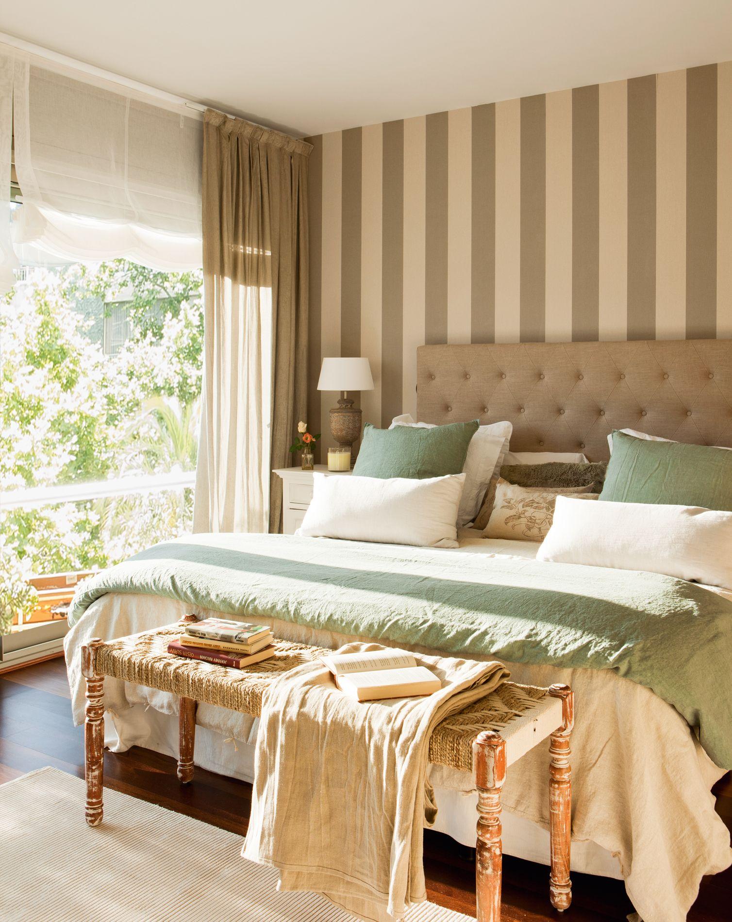 Dormitorio con papel pintado a ryas y cabecero tapizado capiton
