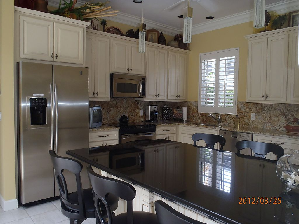 Another view of seating/island. Wall color is a nice contrast with the stainless steel, white cabinets,black island top, and counters and granite backsplash.