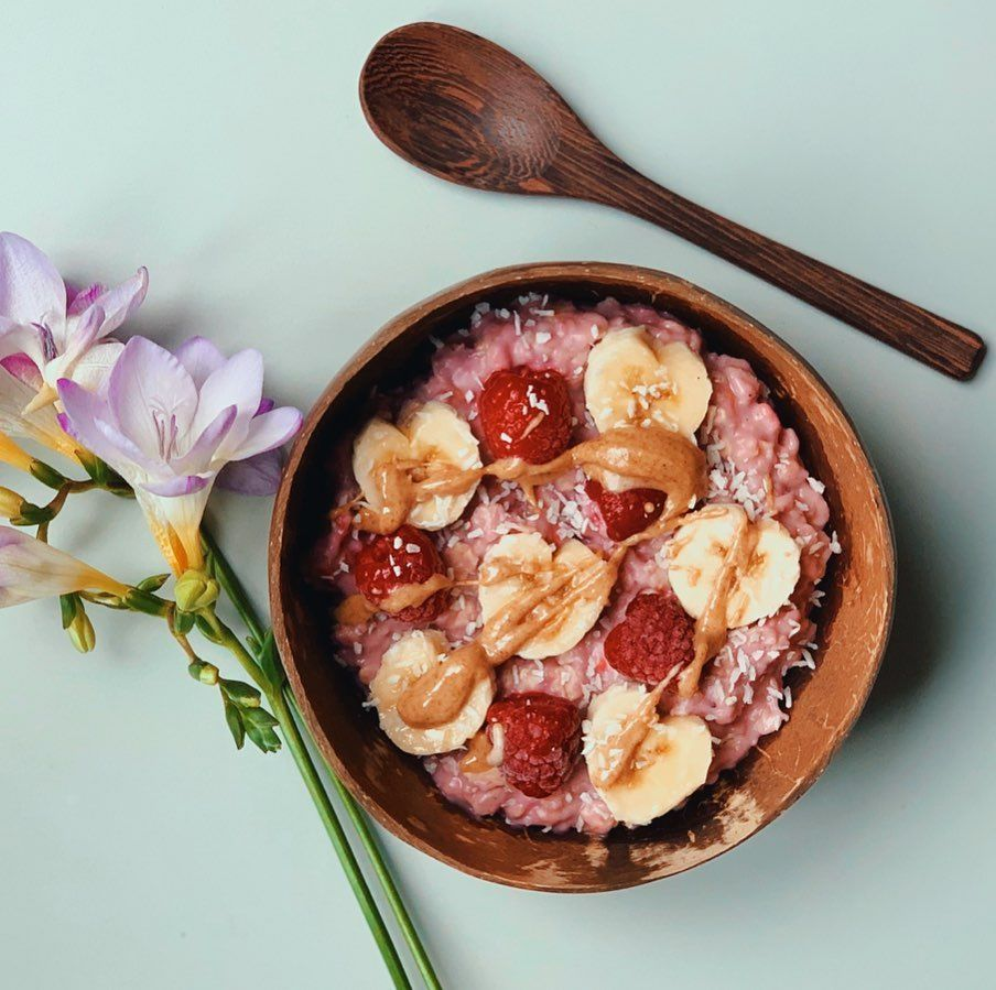 tried something a little different and cooked my oats with a mix of almond milk, @nushfoods blueberry almond yogurt, and some frozen raspberries which gave it this fantastic colour 😍 feeling about 6 again when my favourite thing about this breakfast is that it's pink 😂 topped with banana, raspberries and (of course) drizzle of @pipandnut peanut butter! -
