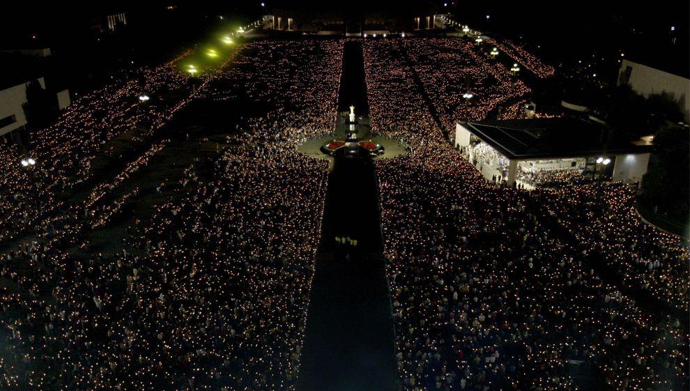 Peregrinos sostienen velas durante una procesión en el santuario católico de Fátima, la noche del domingo 12 de octubre de 2008, en Fátima, Portugal central. Asistieron miles de peregrinos las celebraciones del aniversario de Fátima, donde tres niños pastores afirmaron la Virgen María se les apareció en 13 de mayo y 13 de octubre de 1917.