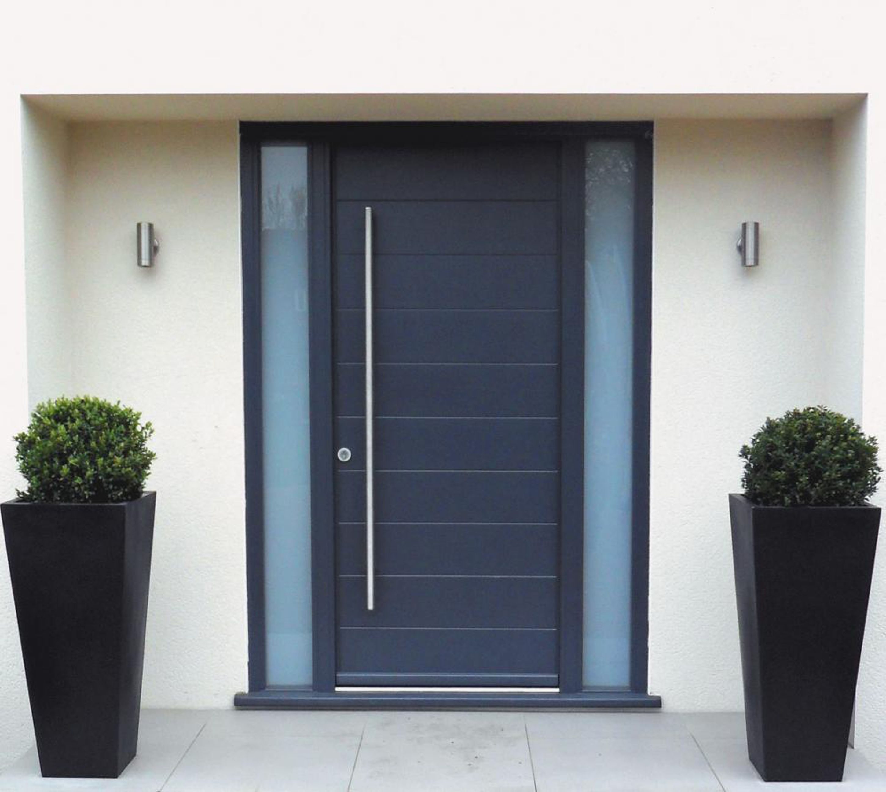 A Navy Blue Door With Oversized Hardware Is Flanked By Black Boxwood Planters And Minimal Silver Sconces