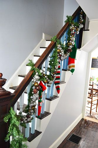 Christmas stair decor with garland, jingle bells, and stockings.