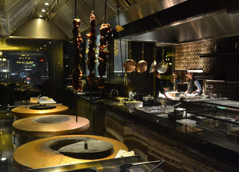 open kitchen design with tandoor ovens at maya indian restaurant
