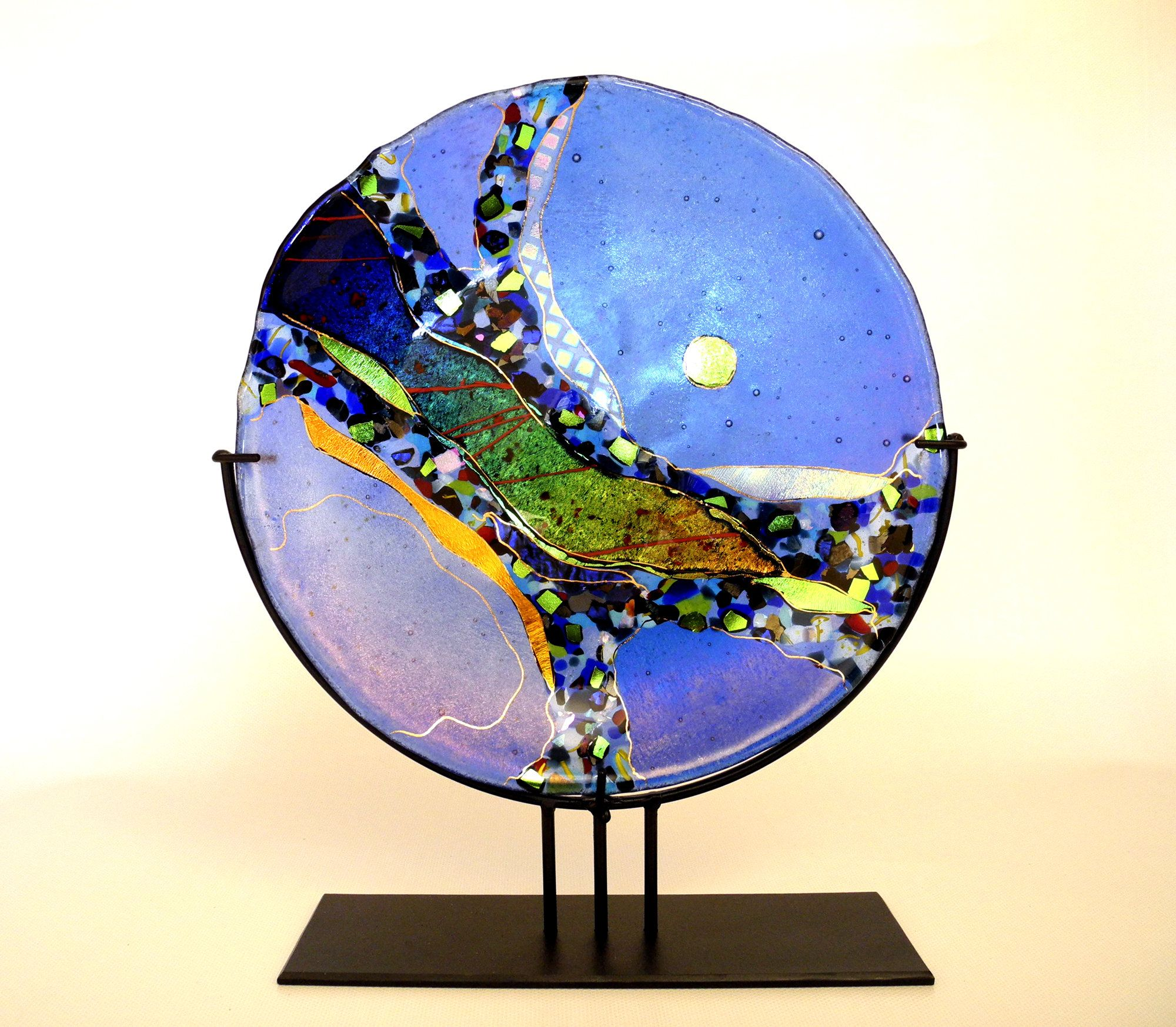 Small Opal Blue Abstract Platter by Karen Ehart. Rivers of *dichroic glass* in many layers and mosaic-like chips of colorful *iridized:iridized glass* and dichroic glass flow through this *fused:fused glass* and *slumped glass* platter with gold pen work. This piece comes with an acrylic stand for display. No two pieces are alike, each are individually designed.