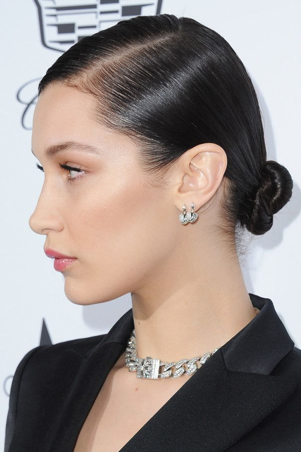 331551cd2d9 For Bella's sleek and refined bun, use a rat-tail comb to create a deep  side part starting above the arch of one brow. Apply a styling cream then  brush hair ...