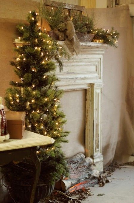 Loving the wood in the fireplace with lights! Christmas faux mantle