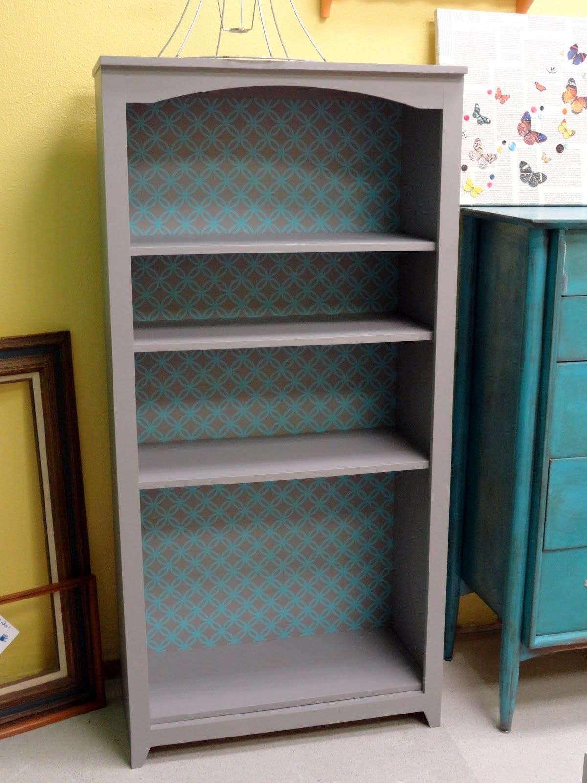 Painted bookcase with wallpaper background