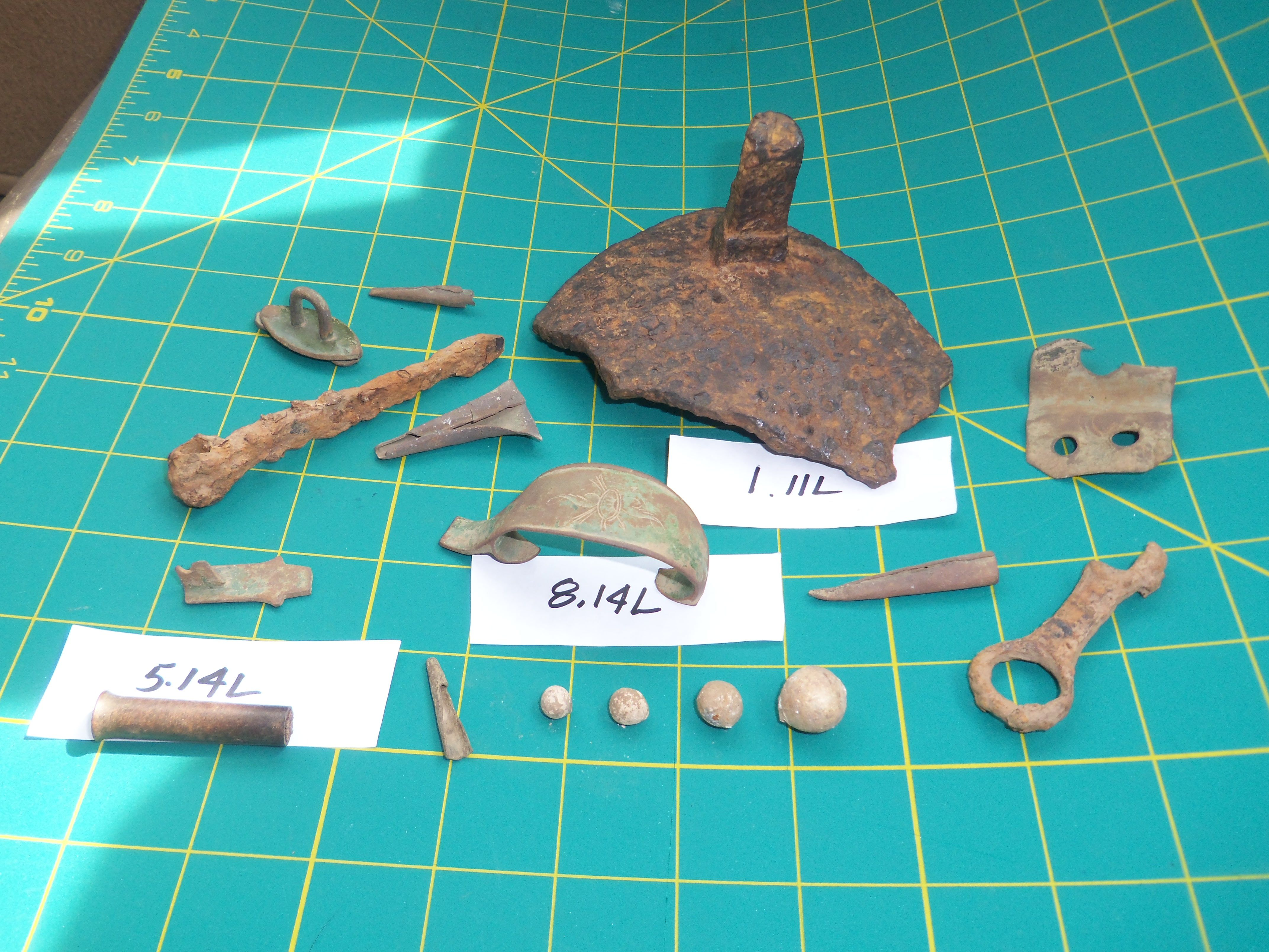 An assortment of Artifacts recovered at a Native American Site in Northeast Ohio. U.S.A. center top; A Iron Kettle Lug, center; A British Trade Rifle Trigger Guard; bottom left; Brass Ram Rod tip.
