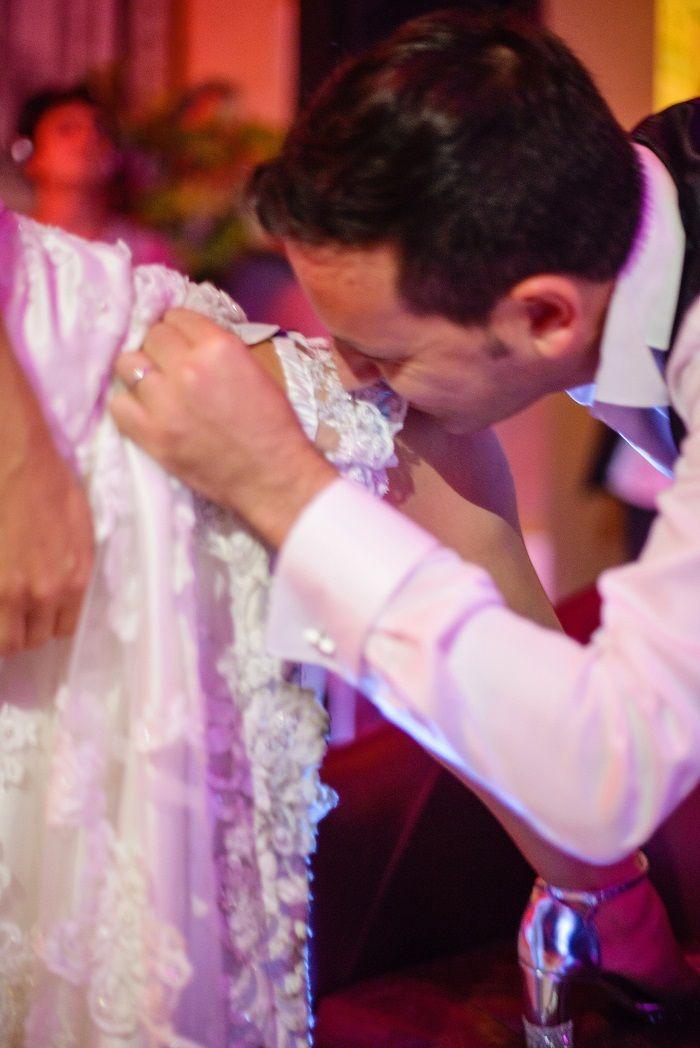 Groom taking off bride's garter | Romantic Rome Garden wedding | Fab Mood