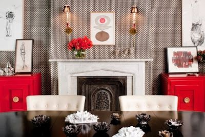 I love the look of this dining roo with the upholstered walls, bright red sideboards and elegant sconces above the fireplace mantel. design :: celerie kemble