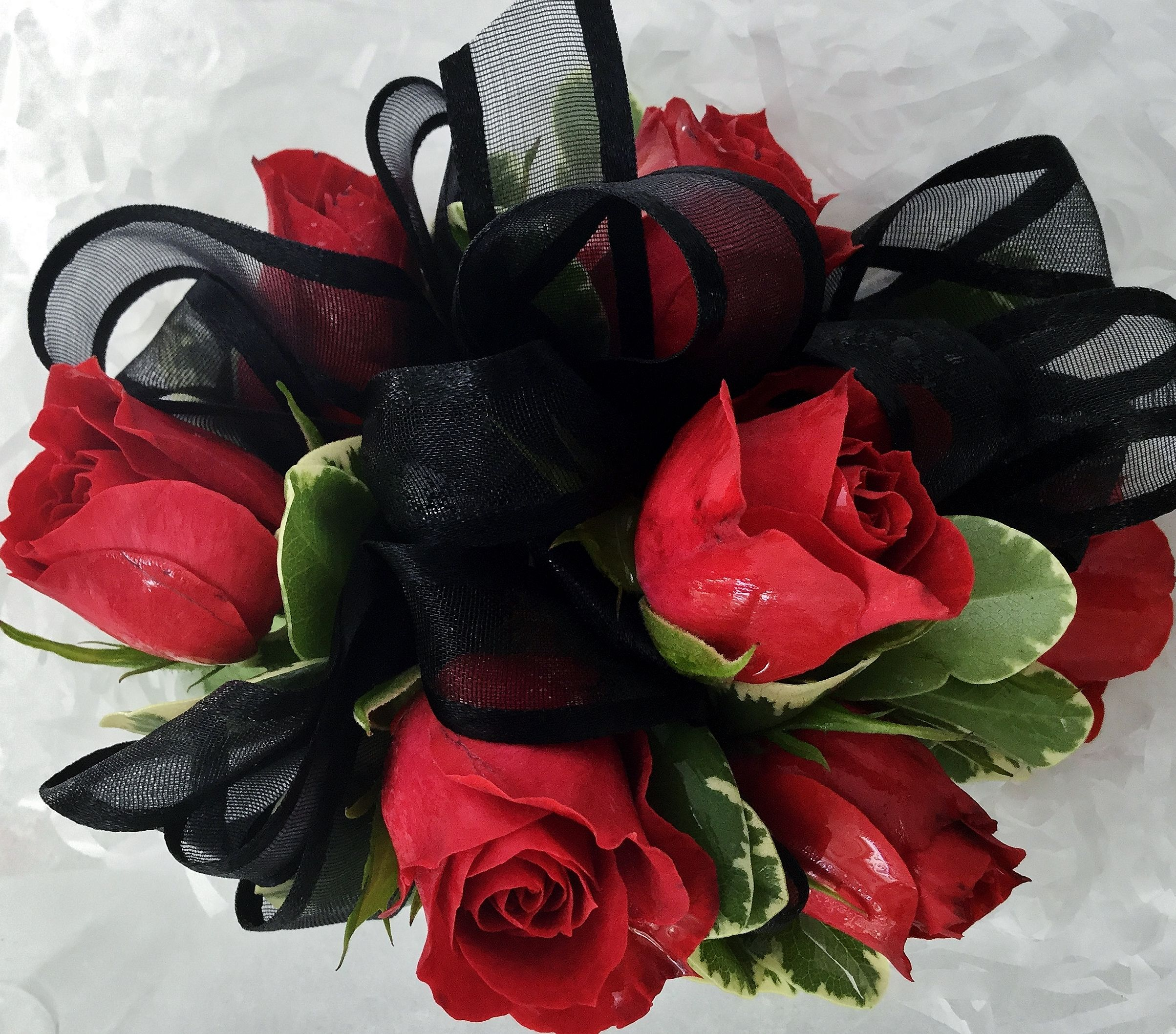 A Beautiful Corsage Made Of Red Sweetheart Roses With A Black Ribbon