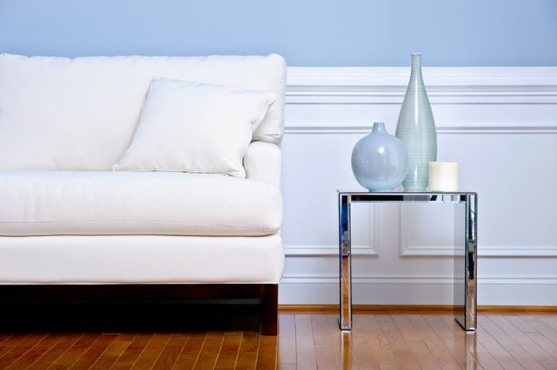 White couch and side table with blue vases, in a blue walled living room with white wood panelling