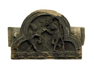 Wooden architectural fragment (panel) from the Kashmir Smast Cave. This decorated beam element, in the shape of a trefoil arch, depicts a dancing ascetic - perhaps Śiva - accompanied by musicians. The central figure is shown in the traditional 'tribhanga' pose, with the body bent in three different directions: 1) head and neck, 2) trunk and 3) legs. The small dentils at the