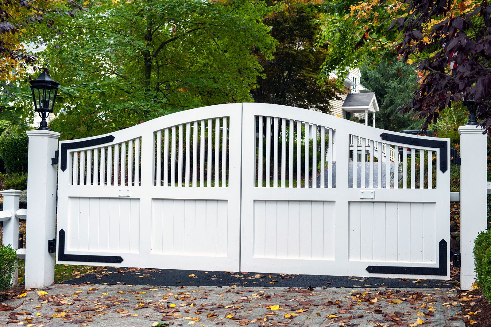 Classic White Wood Driveway Entry Gate With Black Iron Details And Black Carriage Lighting For The Posts Desi Wooden Gates Driveway Entry Gates Entrance Gates