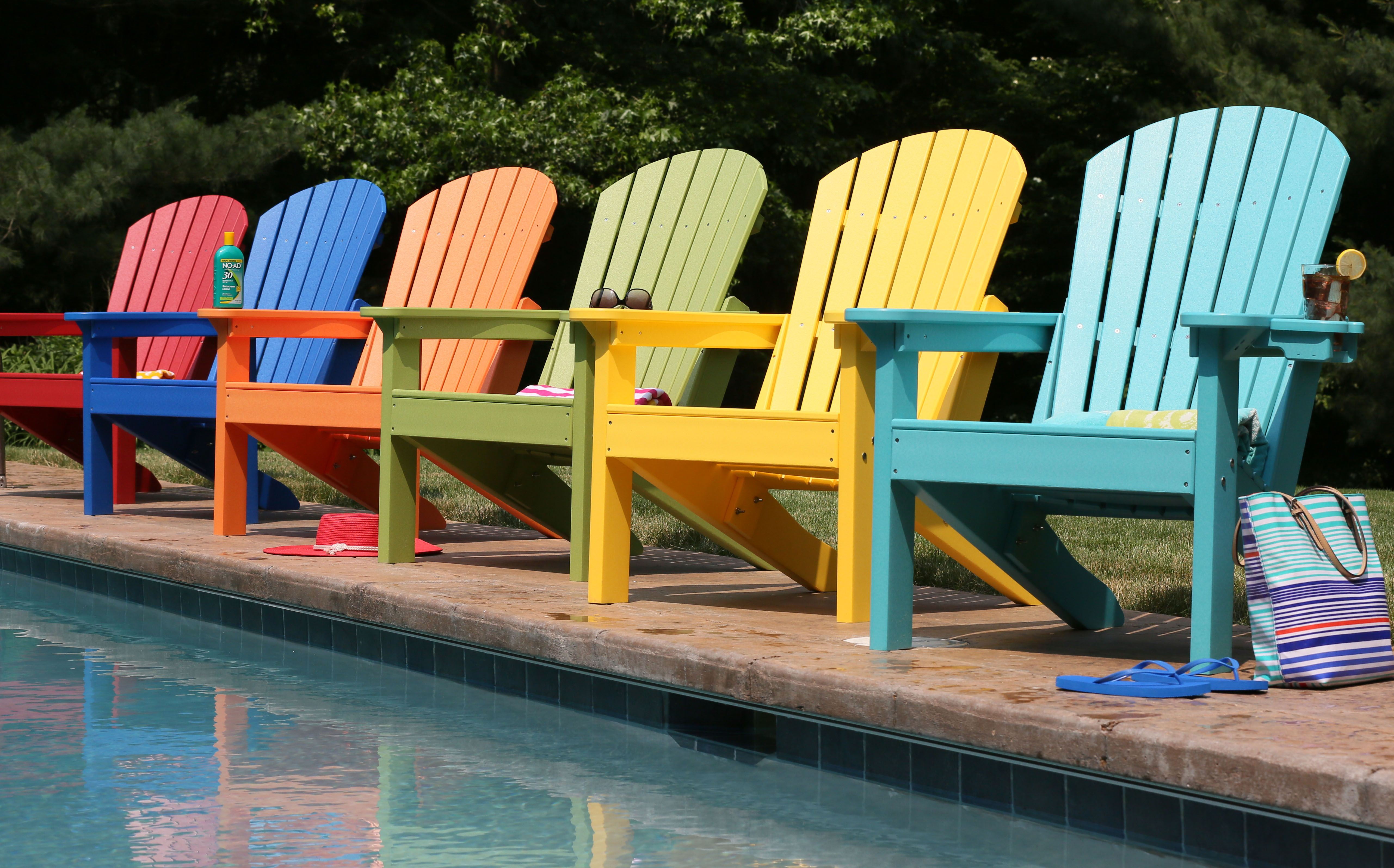 A Poolside Is Turned Into A Relaxation Spot With Bright Colored Adirondack  Chairs. These Poly Lumber Chairs Are Unaffected By Normal Or Saltwater  Pools.