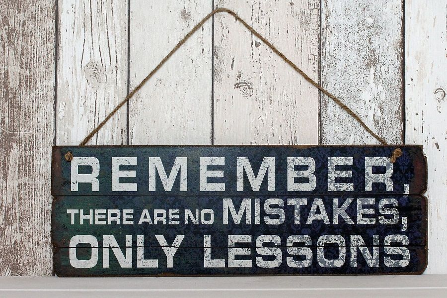 Wooden shabby chic sign hung on rustic twine. `Remember there are no mistakes only lessons`