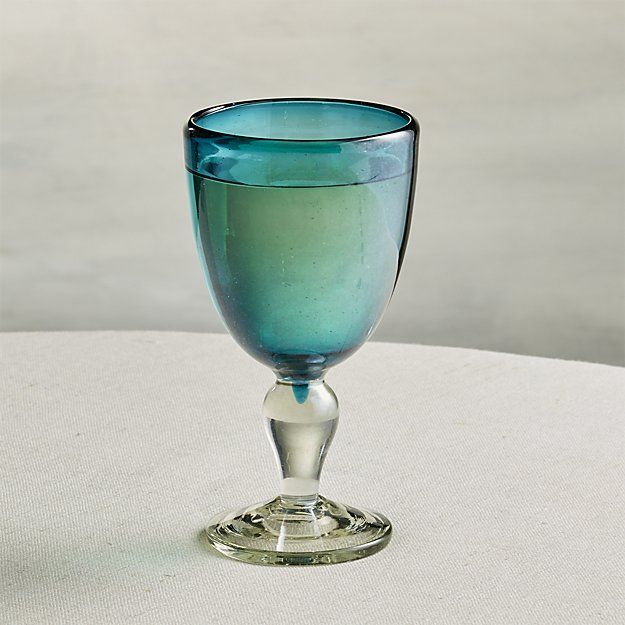 Refined old world shapes shine in two-toned glassware designed by Aaron Probyn. Each handcrafted glass is blown in Mexico of recycled glass imported from France, glass renowned for its clarity and lack of the green tint typically seen in recycled glass. Blue-tinted glass forms the bowl to which a clear stem is attached. Once cooled, glass is given a subtle luster finish.