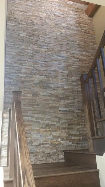 interior stairwell stone accent wall. Stone pictured is Sierra ShadowStone from RealStone Systems. Installed by the pros at Brighton Stone & Fireplace