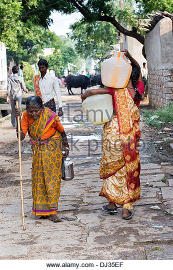 Indian woman plastic water pots from a standpipe in a rural Indian village street. Andhra Pradesh, India - Stock Image
