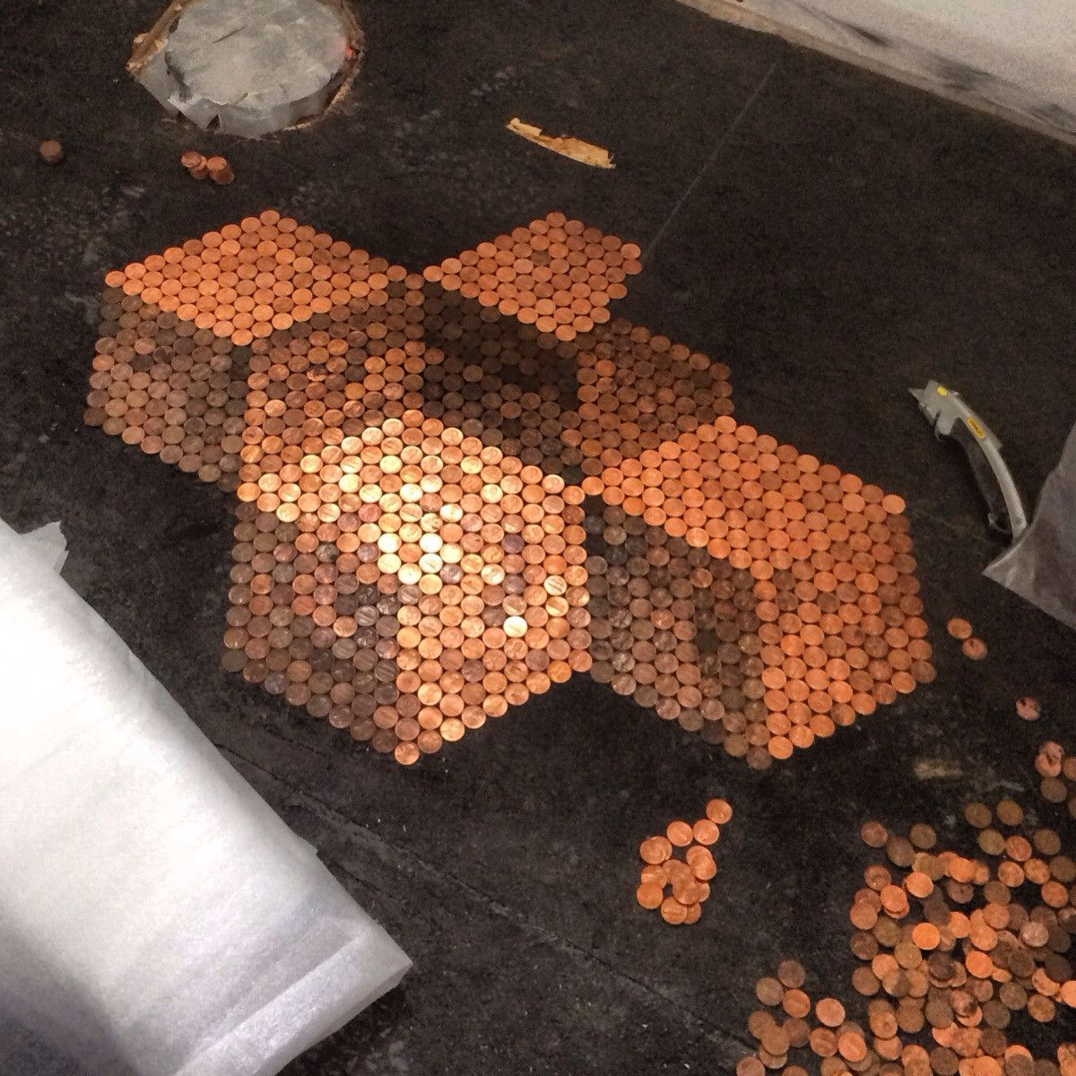 Using pennies to tile my bathroom floor. Here's what I have so far.