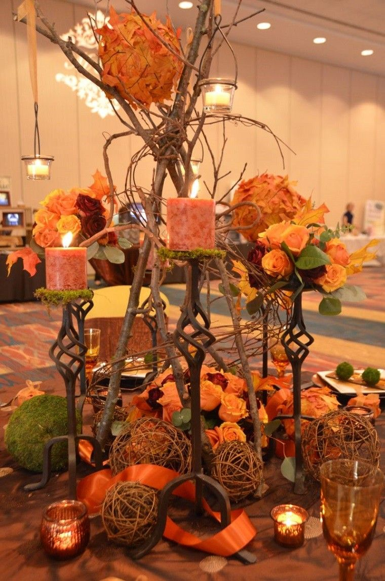 mesa decorada con ramas velas y hojas
