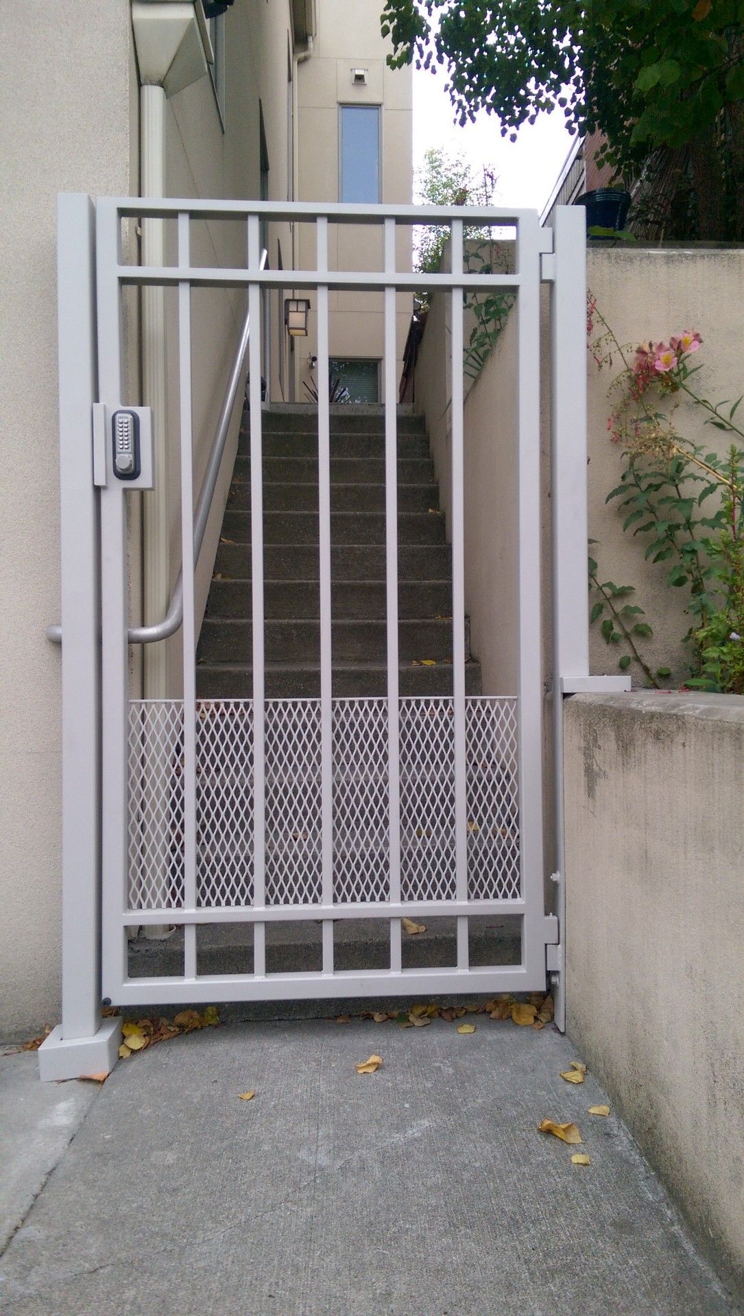 Pedestrian gate with combination lock system painted gray to