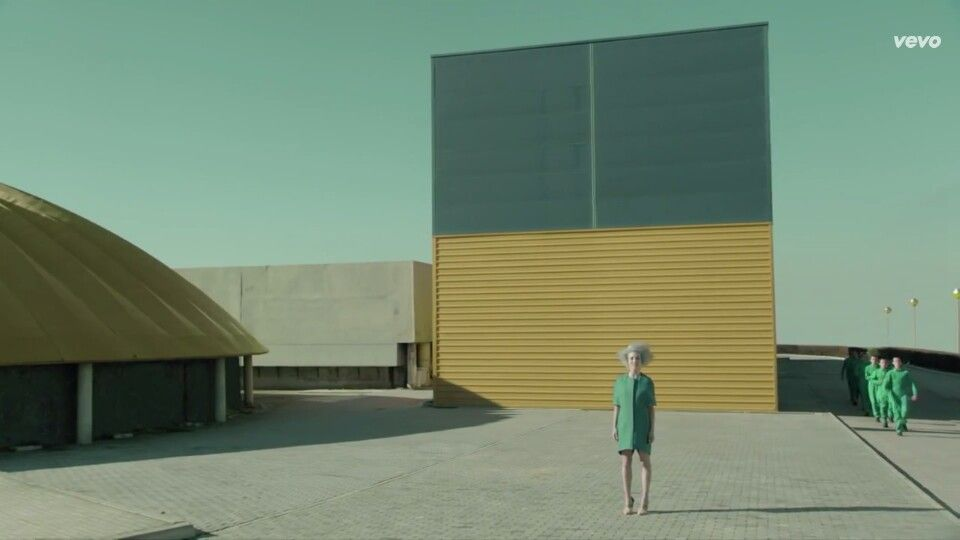 In this picture,  the main girl is standing in a all green dress in front of a yellow building.  The horizontal lines on the building is a good design because it gives it texture. There is also a circular building next to it with vertical lines, giving the viewer different details.  The people walking in a straight line are known to be behind because of there size, also wearing green showing that they may be equal.
