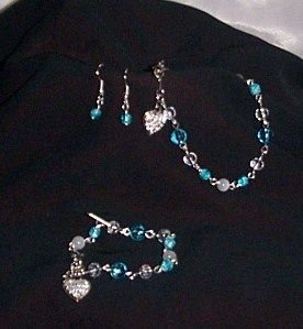 """6"""" - 7 1/2"""" Child Bracelet, 8 1/2"""" Adult Bracelet, & Fish Hook Earrings. Silver-toned bracelets made with blue clear beads, clear beads, white fiber optic rounds, & blue glass beads that have a crackle design. They each have a lobster clasp and heart shaped pendant with white rhinestones on it and are completely hand-tooled. I made the child's bracelet adjustable. The fish hook style earrings are made with the small blue crackle beads. This set would also be great for a flower girl and …"""