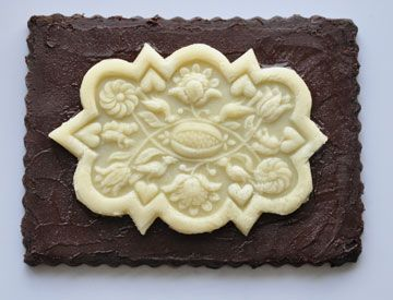 Dark chocolate cookies with molded marzipan topping, created with a springerle mold.