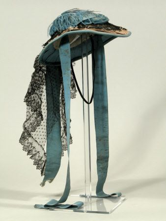 ~1865-1870 Hat made from straw plait and hand stitched through overlapping plait in a spiral from the crown center. The brim is faced with turquoise blue ribbed silk with a separate head and side lining. It is wired at the edge of the brim. It is trimmed with a twisted blue velvet ribbon and ribbed silk ribbon. There is a frill over the brim of black machine lace and cream silk lace. There is one blue ostrich feather over the crown. Via National Trust~
