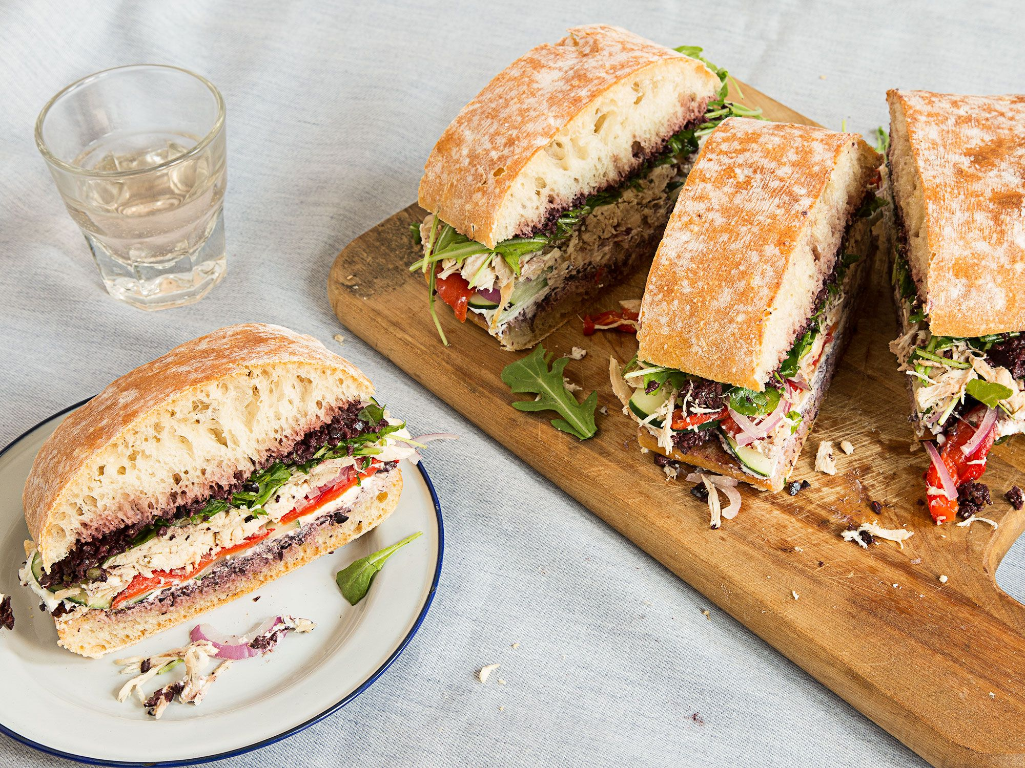 This hearty twist on the classic Provençal pressed sandwich pan bagnat combines black olive tapenade, goat cheese, roasted chicken, and thinly sliced vegetables.