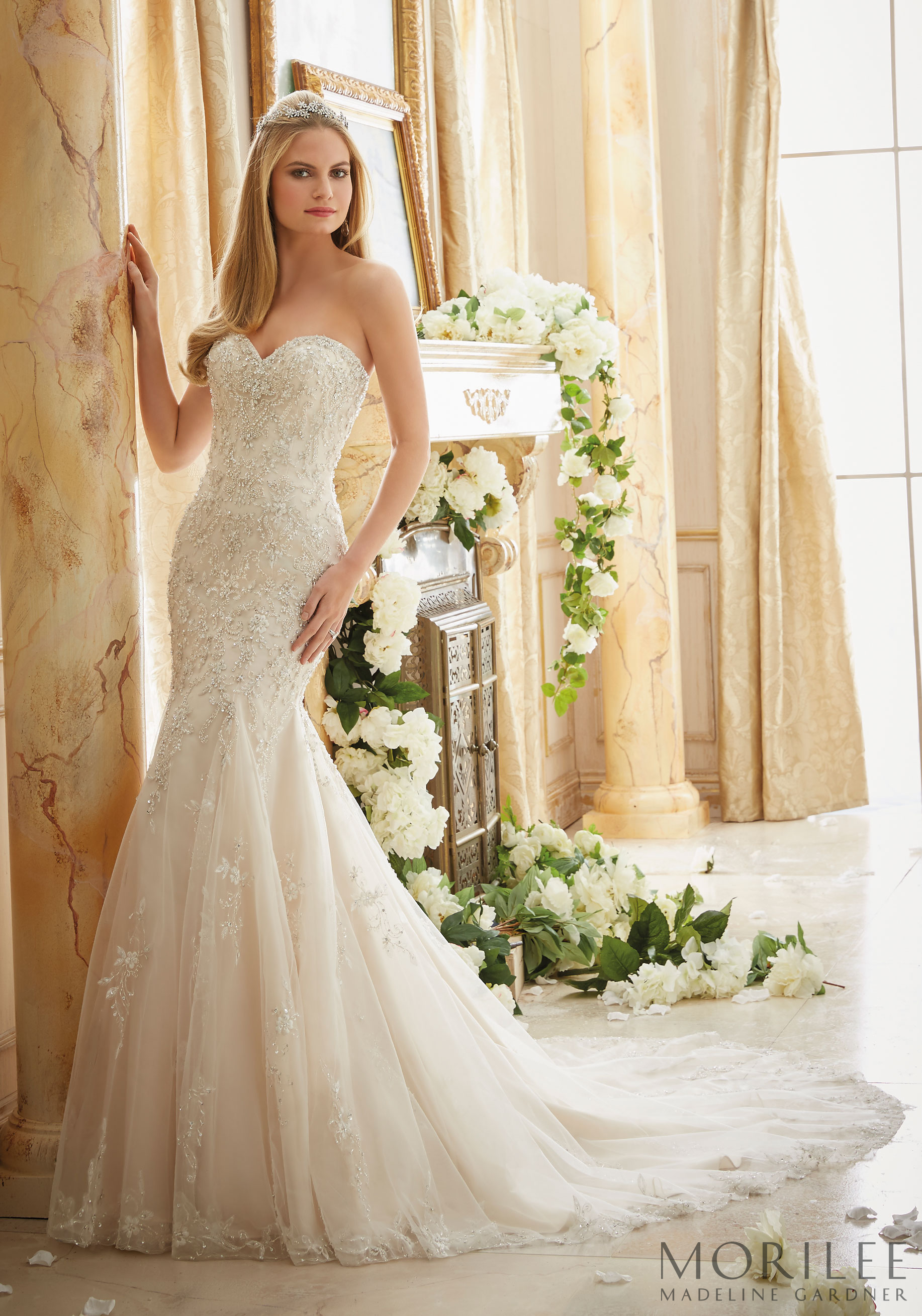 Delicate floral lace sweeps the skirt and train of this gorgeous