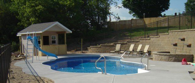 ornamental aluminum fence around swimming pool and atop retaining wall in Sparta, MI