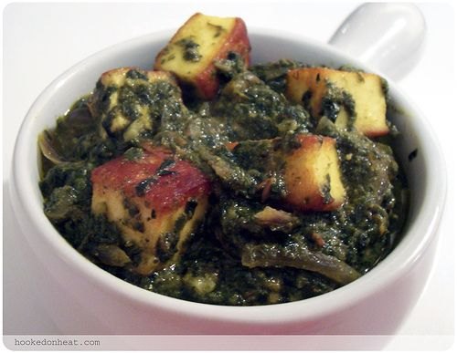 Palak Paneer - PSed by Meenakshi Agarwal, via Flickr PALAK PANEER Prep time: 20 min, Cooking time: 15 min | Serves: 4 1 large bunch of fresh spinach 500 gms of Paneer, cut in 1-inch cubes and fried till brown 1 medium-sized onion, thinly sliced 1 small tomato, finely chopped 1-inch sized ginger, sliced  	 1 tsp cumin seeds 1 tsp coriander seeds 2 tbsp plain yoghurt salt, to taste 1/2 tsp red chilli powder 1/2 tsp coriander powder 2 tbsp light cooking oil