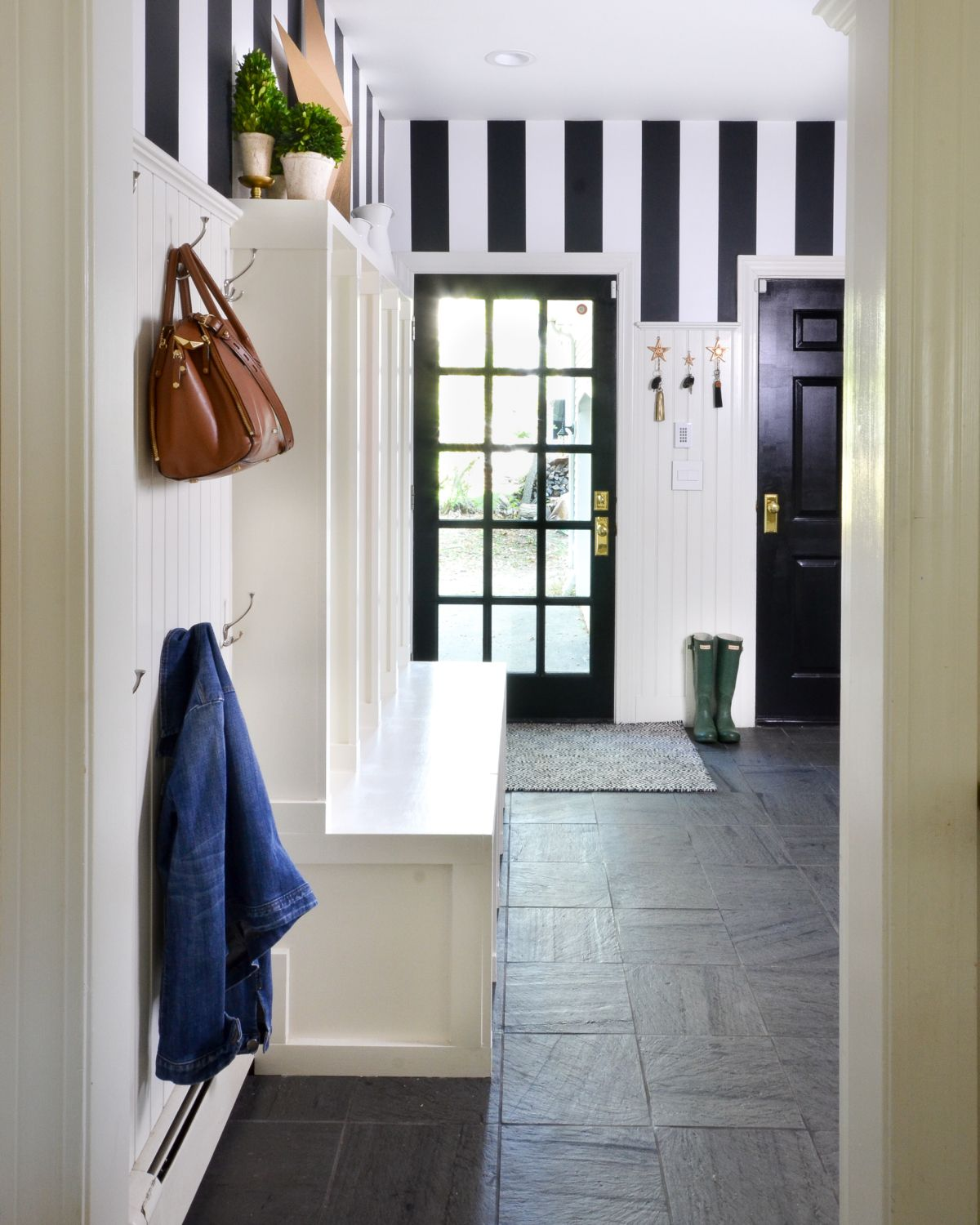 Black and white mudroom with striped wallpaper beadboard custom