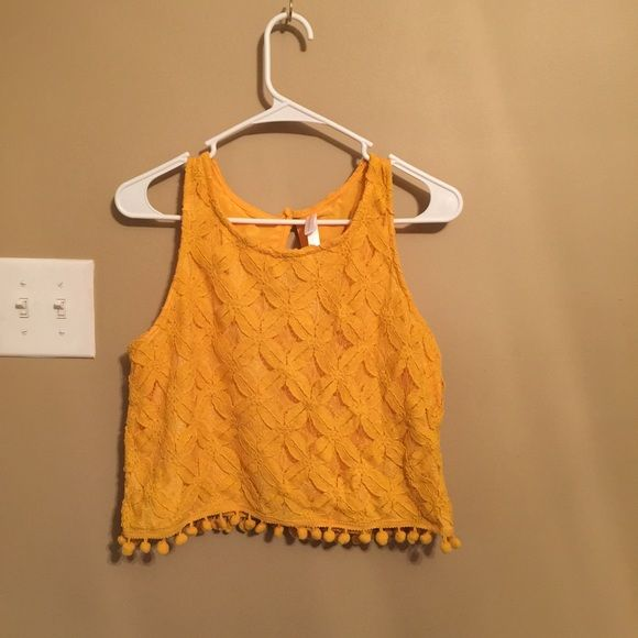 Yellow floral pattern cropped top Yellow floral pattern cropped top with Pom Pom at the end. NWT. No stains or holes. Cute with high waisted bottoms. No trades. I sell on mercari too! Xhilaration Tops Crop Tops