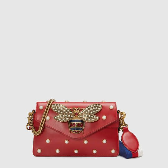 Shop the Broadway leather clutch by Gucci. A mini bag with pearl studs and  metal bee detail. The bee s striped body is highlighted with blue enamel  and red ... b77e0cf5cb205