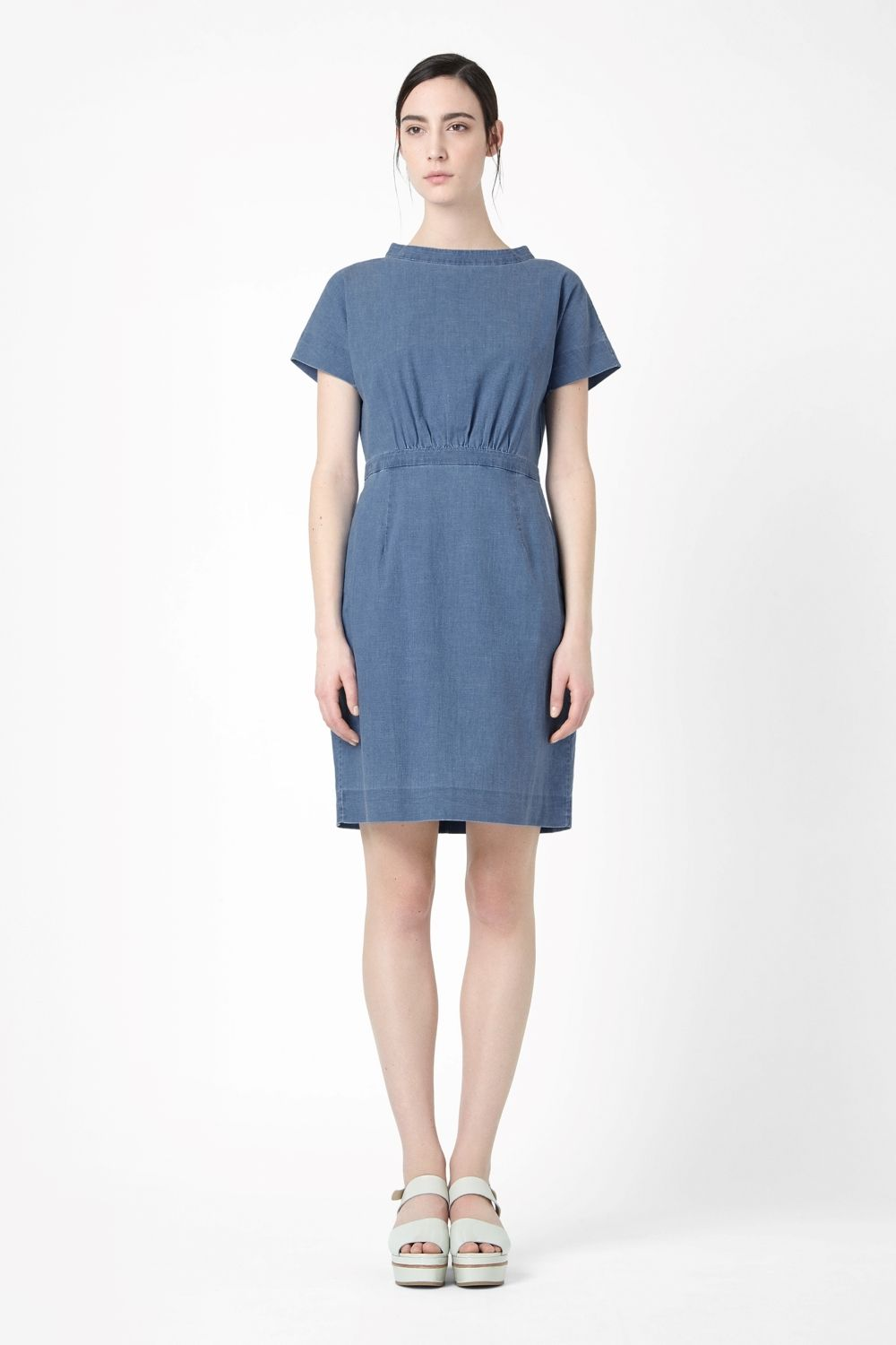 Made from lightweight cotton chambray with a washed denim quality, this casual dress has a wide raised collar, hidden back zip and a fitted waistband for a flared silhouette. This dress was made with a special dye process, so each one is a little different from the next.