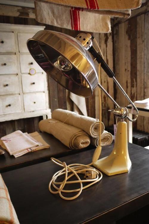 A vintage desk lamp along with rustic linens.