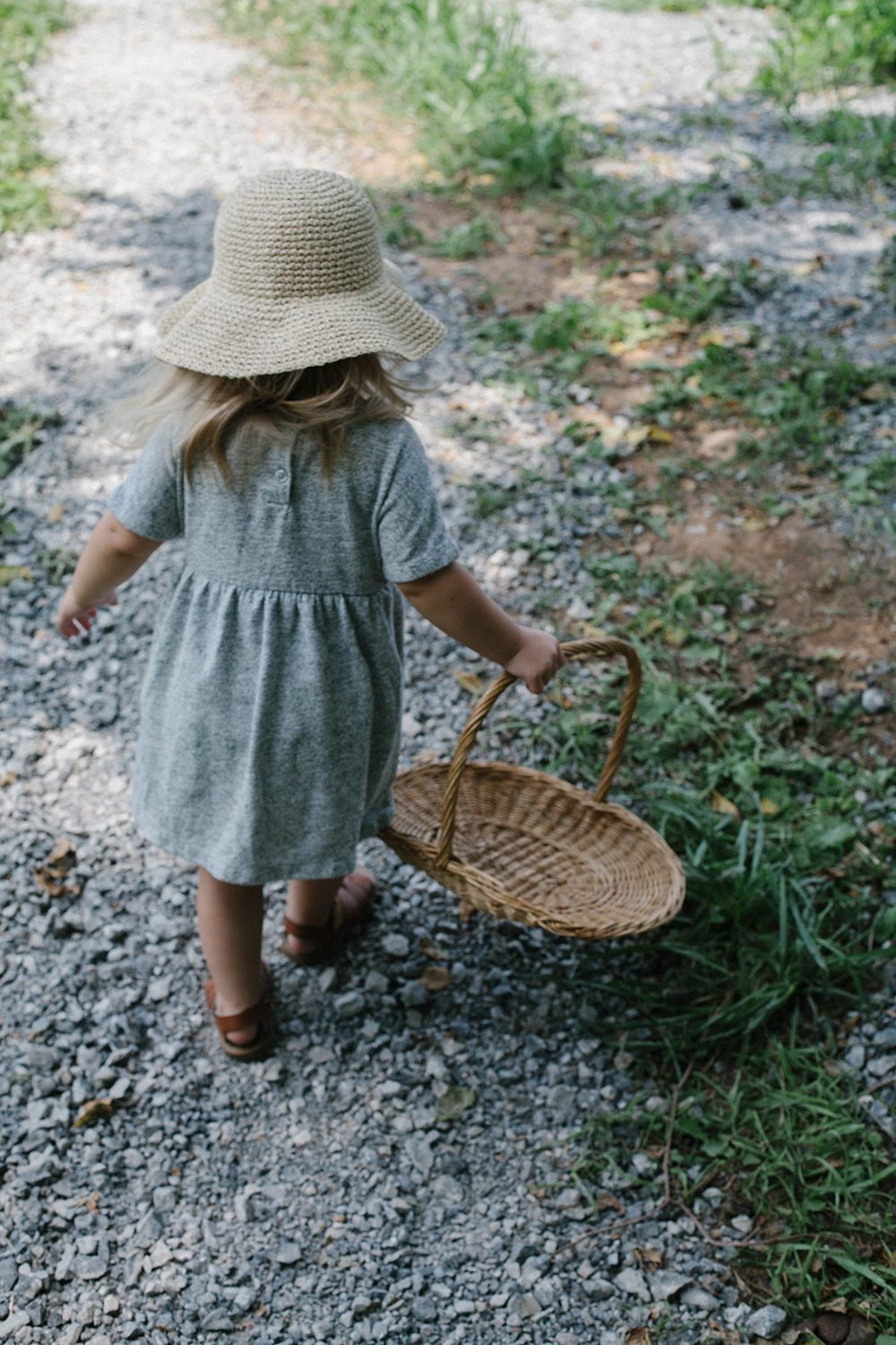 Little girl in a jean dress and sun hat carrying a basket down a gravel pathway