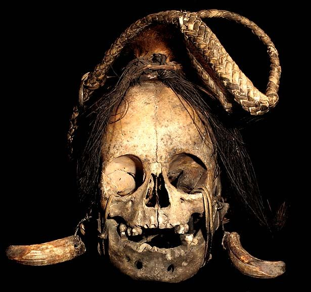 IFUGAO TRIBE: HEAD HUNTING TROPHY SKULL #7  RATTAN CARRYING HANDLE, BOAR TUSKS,  BOAR HAIR, ANIMAL TAIL, HUMAN SKULL.  THE IFUGAO TRIBE, FROM THE PHILIPPINES, PLACE HEAD HUNTED  HUMAN TROPHY SKULLS OUTSIDE OF THEIR HUTS, AS WELL AS,   MOUNT THEM OVER THEIR HEARTHS INSIDE OF THEIR HOMES.