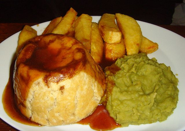 Freshly baked individual meat pie decorated with poppy seeds and served with chips peas and gravy.