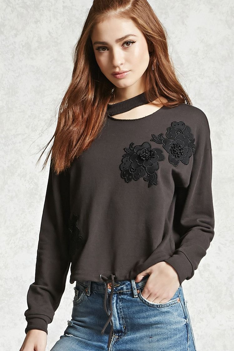 A French terry knit pullover featuring a round neckline with a cutout, embroidered flower graphics on the front, long dropped sleeves, ribbed trim, and a drawstring hem.