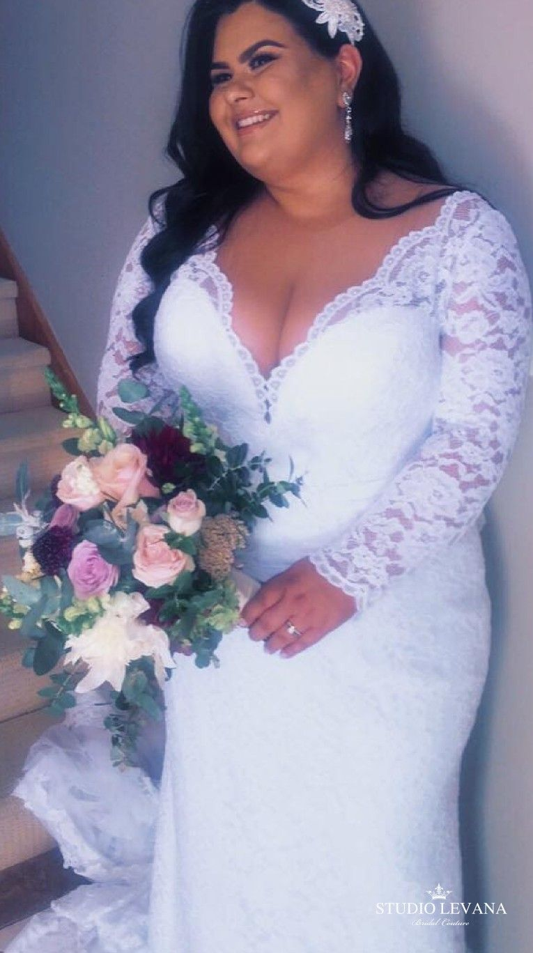 Plus size mermaid wedding dress with long sleeves on a real bride