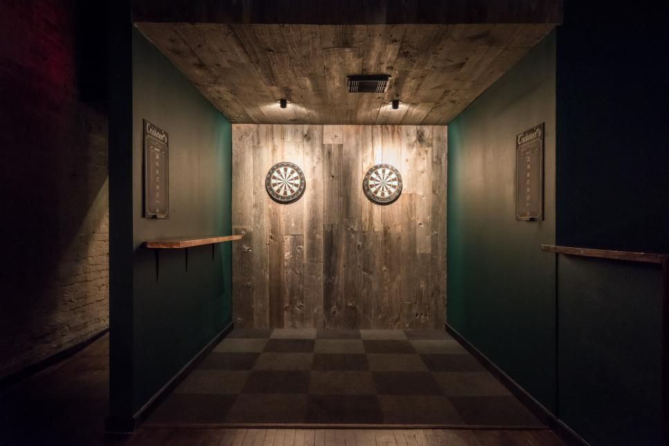 Dark green walls pop against the natural hardwood wall and ceiling in this dart nook. A checked floor gives the space a classic diner look. Two mounted ceiling lights cast a spotlight on each of the dart boards to highlight them in the dim space.