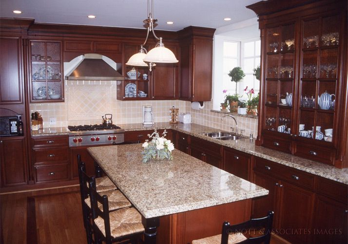 stained cherry wood kitchen cabinets and marble island in south