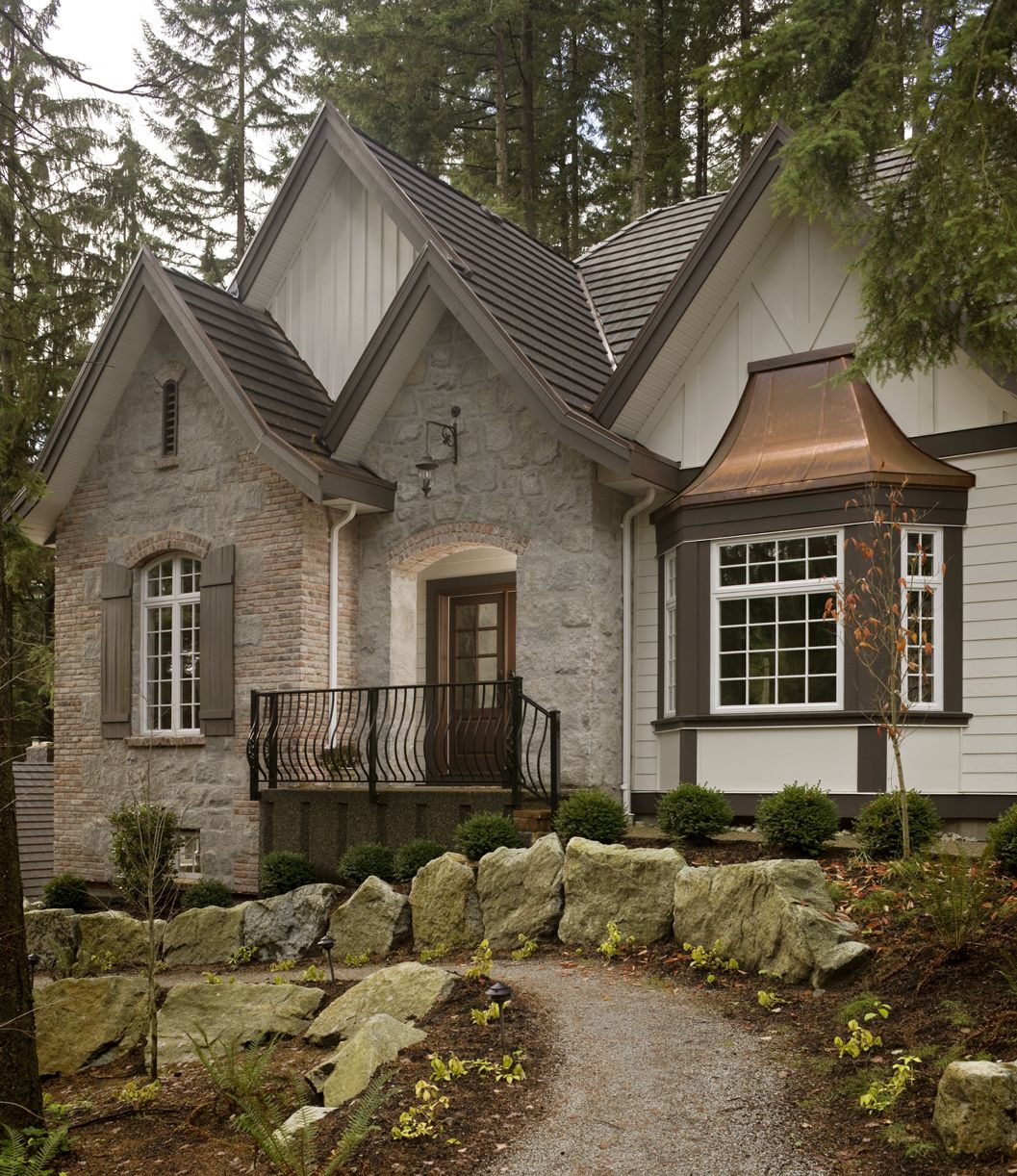 A Grey Stone Home Exterior With Iron Guardrail And Copper