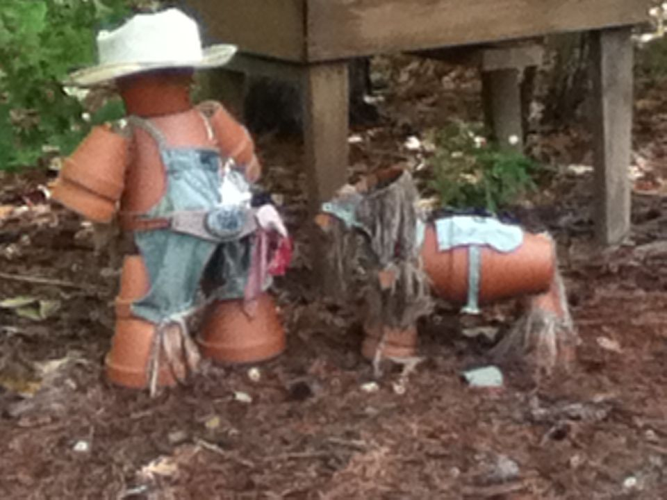 Take flower pots and stack them to make a flower pot man for Things you can make with horseshoes